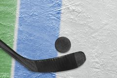 Hockey stick, puck and fragment of the ice arena with green and blue lines. Hockey accessories on the ice hockey arena. Concept, hockey, wallpaper stock photography