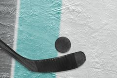Hockey stick, puck and ice arena fragment with black and blue-green lines. Hockey accessories on the ice hockey arena. Concept, hockey, wallpaper stock photo