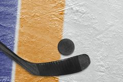 Hockey stick, puck and ice arena fragment with blue and orange lines. Hockey accessories on the ice hockey arena. Concept, hockey, wallpaper stock images