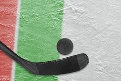 Hockey stick, puck and ice arena fragment with red and green lines. Hockey accessories on the ice hockey arena. Concept, hockey, wallpaper stock image