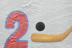 Hockey stick, puck and the numeral two Stock Photos