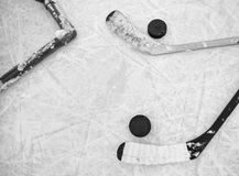 Hockey sticks and pucks. Two hockey sticks and pucks laying on textured ice skating rink in black and white Stock Photography