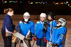 Hockey team listens to coach explaining game plan. Hockey team listening to coach explaining game plan at ice rink diagram stock photo