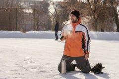 Hockeyamateurgetränktee auf der Thermosflasche an der Eisbahn stockbilder