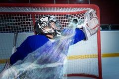 Hockeygoaliemiss pucken Arkivfoto