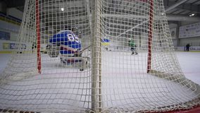 Hockeylandung, Tormann mit Hockeyschläger fällt und fehlender Kobold im Tor vom Gegner auf Eisbahn aus stock video
