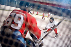 Hockeymatch am Eisbahnenspieler greift Torhüter an lizenzfreie stockfotografie