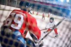 Hockeymatchen på isbanaspelaren anfaller målvakten royaltyfria bilder