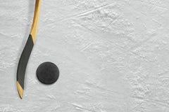 Hockeypinne och puck på isen Arkivbilder