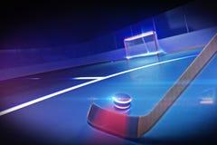 Hockeypinne och puck på isisbanan Arkivbild