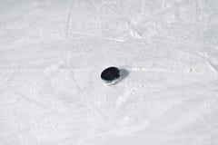 Hockeypuck på isisbana Arkivfoto