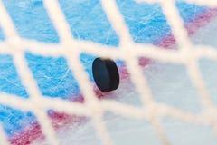 Hockeypucken till och med mål förtjänar Royaltyfria Bilder