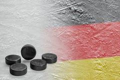 Hockeypucks en het beeld van de Duitse vlag op het ijs royalty-vrije stock foto