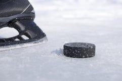 Hockeyskridsko och puck Royaltyfri Foto