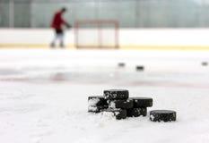 Hockeyspelare med bunten av puckar royaltyfria foton