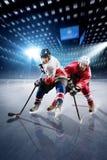 Hockeyspelare skjuter pucken och anfaller arkivfoton