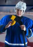 Hockeyspelare som tejpar hans pinne Arkivfoto