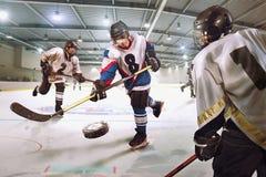 Hockeyspelaren skjuter pucken och anfaller målvakten fotografering för bildbyråer