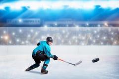 Hockeyspieler mit Stock und Kobold macht einen Wurf lizenzfreie stockfotografie