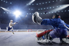 Hockeyspieler schießt den Kobold und die Angriffe Lizenzfreie Stockbilder