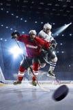 Hockeyspieler schießt den Kobold und die Angriffe Lizenzfreie Stockfotos