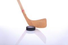Hockeysteuerknüppel und -kobold auf reflektierender Oberfläche Stockfotografie