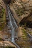 Hocking小山瀑布在有岩石峭壁的森林里 图库摄影