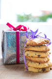 Hocolate chip cookie tied up next to a wrapped up Christmas present. Stock Image