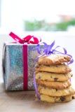 Hocolate chipkaka som binds upp bredvid en slågen in upp julklapp Fotografering för Bildbyråer