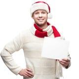 圣诞老人帽子hoding的标志的年轻偶然人 免版税库存照片