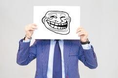 Hoding Karte des Geschäftsmannes mit Schleppangelgesicht auf grauem Hintergrund Stockfotografie
