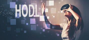 HODL при женщина используя шлемофон виртуальной реальности стоковое фото