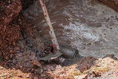 Hoe, in dig hole repair plumbing, with water motion. Selective focus hoe, in dig hole repair plumbing, with water motion the pipe severe Stock Photos