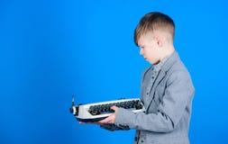 Hoe het retro het typen machinewerk  Slim kind die retro technologie gebruiken Leuke jongen met schrijfmachine Klein jong geitje stock fotografie