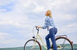 Hoe te om fiets als volwassene leren te berijden De vrouw berijdt de achtergrond van de fietshemel Actieve vrije tijd De fiets va royalty-vrije stock foto's