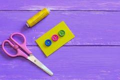 Hoe te op een knoop met vier gaten te naaien Gekleurde knopen op geel gevoeld stuk Schaar, draad, naald op een houten achtergrond Royalty-vrije Stock Foto