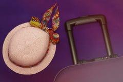 Hoed en koffer op een lilac achtergrondtoerismereis stock foto