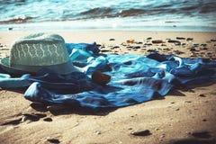 Hoed en stranduniformjas op het strand met het overzees op de achtergrond stock afbeelding