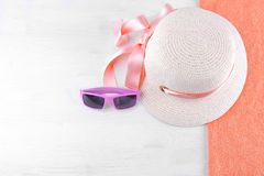 hoed met een roze lint en roze zonnebril op een oranje handdoek Witte houten achtergrond, hoogste mening stock foto