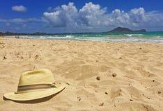 Hoed op een zandig strand met mensen in de achtergrondavonturenreis Stock Afbeeldingen