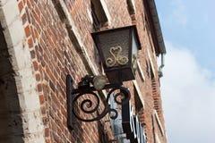 HOEGAARDEN, BÉLGICA - 4 DE SETEMBRO DE 2014: Lâmpada de rua do ferro do vintage na parede de uma construção de tijolo vermelho ve Foto de Stock