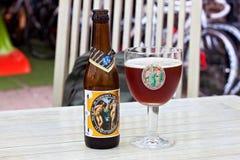 HOEGAARDEN, BELGIEN - 4. SEPTEMBER 2014: Füllen Sie und das Glas des ` Hoegaarden-` De Verboden Vrucht Fruchtbieres ab Stockbild
