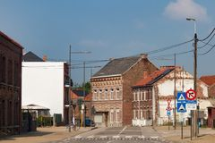 HOEGAARDEN BELGIEN - SEPTEMBER 04, 2014: Gamla byggnader för röd tegelsten i mitten av Hoegaardenen på den Stationsstraat gatan royaltyfri bild