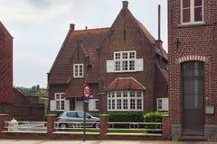 HOEGAARDEN BELGIEN - SEPTEMBER 04, 2014: Gammal byggnad för röd tegelsten i mitten av Hoegaardenen på Ernest Ourystraat Street royaltyfria foton