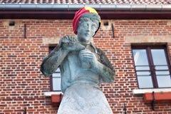 HOEGAARDEN BELGIEN - SEPTEMBER 04, 2014: Skulptur av ett hällande öl för ung man in i en råna arkivbilder