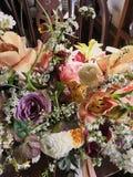 Hoekig boeket van kleurrijke pastelkleurbloemen die zich op houten bank verspreiden royalty-vrije stock afbeeldingen