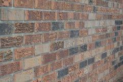 Hoekige bakstenen muur aan het recht stock afbeelding