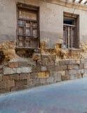 Hoekige mening van twee aangrenzende gebroken vensters en grunge steenbakstenen muur in verlaten Darb Gr Labana, Kaïro, Egypte royalty-vrije stock afbeeldingen