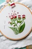 Hoepel modern borduurwerk met botanische motieven op een houten achtergrond Stock Foto