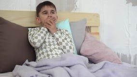 Hoest de zieken weinig jongen terwijl het zitten in bed en behandelt zich met een deken HD stock footage